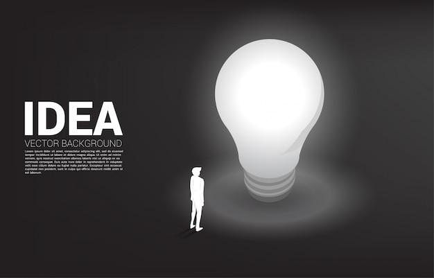 Silhueta do empresário em pé com lâmpada. Vetor Premium