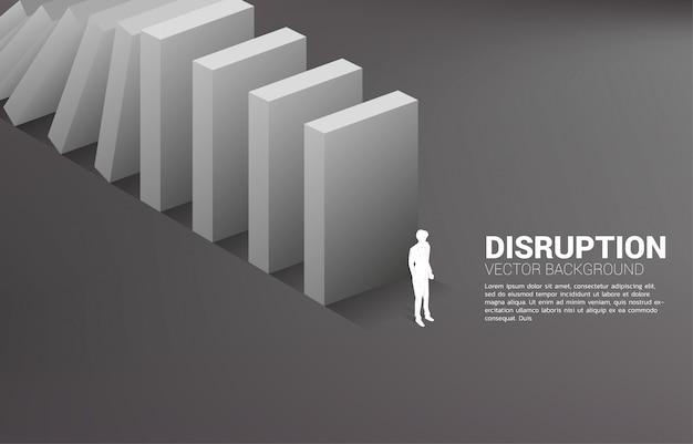 Silhueta do empresário em pé no final do colapso do dominó. conceito de perturbação do setor empresarial Vetor Premium