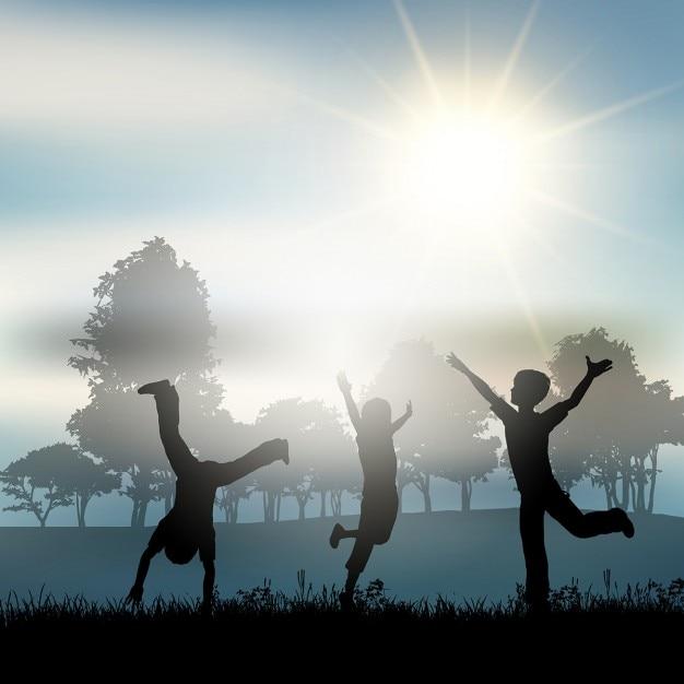 Silhuetas de crianças brincando no campo Vetor grátis