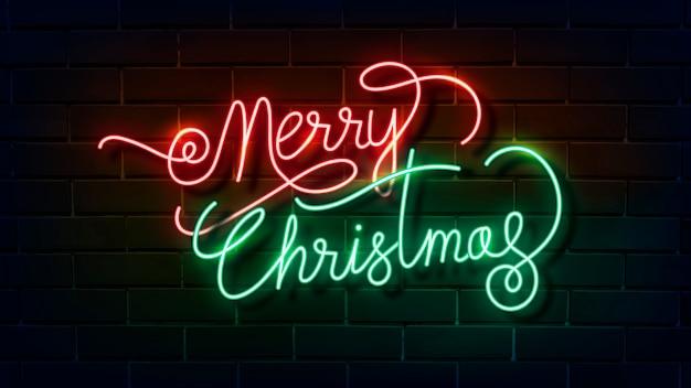 Sinal de néon de feliz natal em uma parede de tijolos escuros Vetor grátis