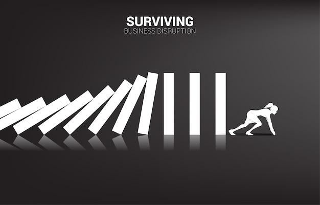 Sobrevivendo à interrupção dos negócios. silhueta de mulher de negócios pronta para fugir do colapso do dominó. conceito de perturbação do setor empresarial Vetor Premium