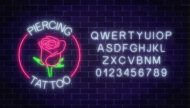 Tabuleta de néon brilhante de tatuagem e piercing salão com emblema rosa e alfabeto Vetor Premium