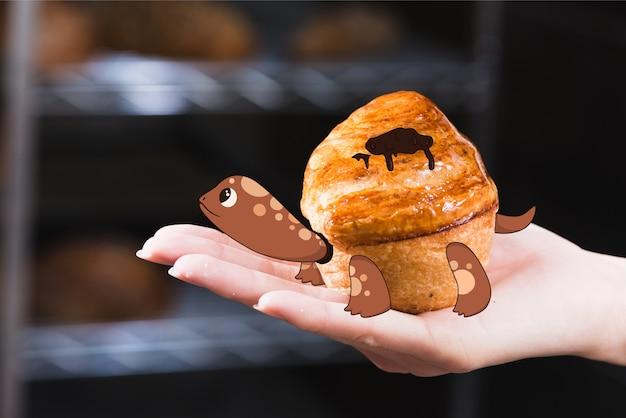 Tartaruga de desenho em um muffin Vetor grátis