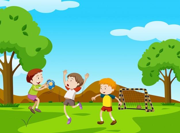 Três meninos jogando bola no parque Vetor grátis