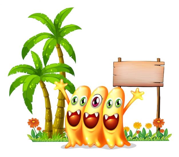Três monstro laranja feliz na frente da sinalização de madeira vazia Vetor grátis