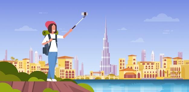 Turista de mulher com mochila, tirando foto de selfie sobre fundo de cidade bonita de dubai Vetor Premium