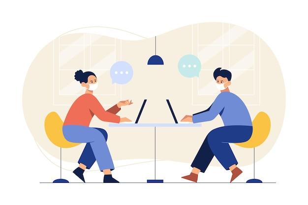 Um homem e uma mulher usando uma máscara e trabalhando com um laptop Vetor grátis