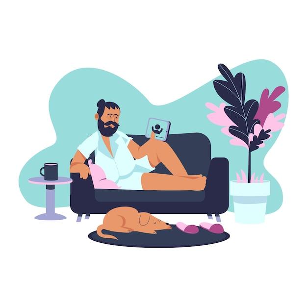 Um homem segurando um tablet relaxando em casa no sofá Vetor grátis