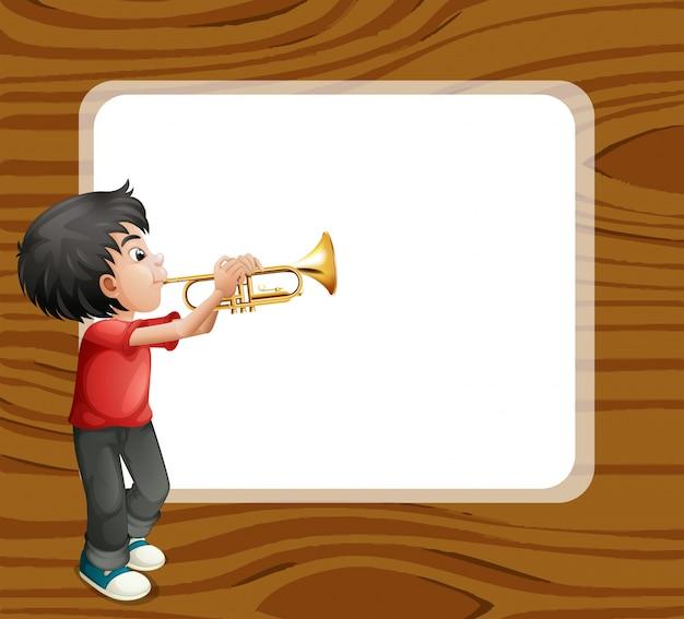Um menino brincando com o trombone em frente a um modelo vazio Vetor grátis