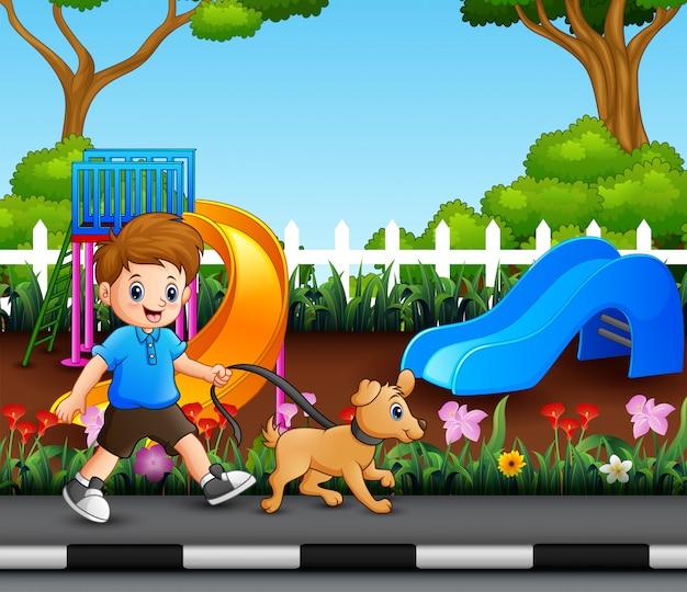 Um menino com seu animal de estimação andando no parque da cidade Vetor Premium