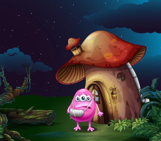 Um monstro rosa ferido perto da casa de cogumelo Vetor grátis