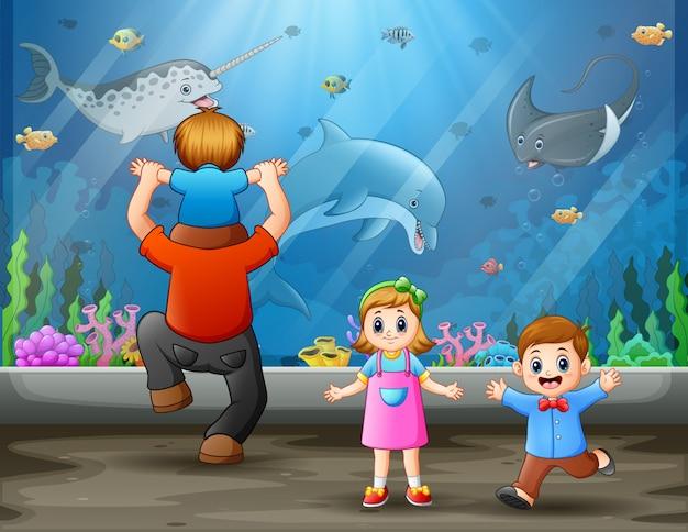 Um pai com filhos olhando peixes nadando Vetor Premium
