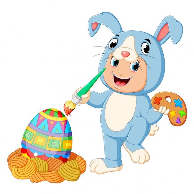 Um rapaz vestindo trajes de coelho e pintar um ovo Vetor Premium