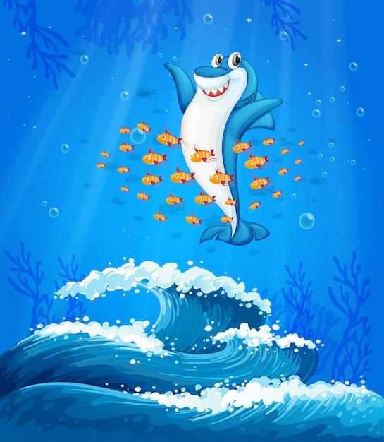 Um tubarão cercado de peixes sob o mar Vetor grátis