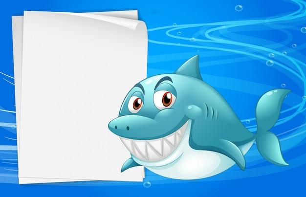 Um tubarão com um papel bond vazio sob o mar Vetor grátis