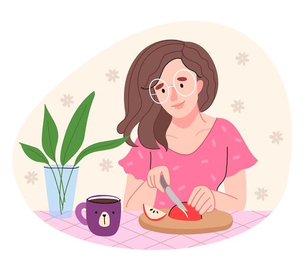 Uma garota com uma camisa rosa está cozinhando na cozinha. mulher de óculos redondos corta uma maçã. Vetor Premium
