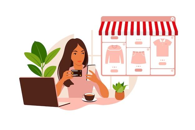 Uma jovem está fazendo compras online usando um laptop. pague as compras com cartão de crédito pela internet. o conceito de pagamentos online e compras eletrônicas, compras. plano. Vetor Premium