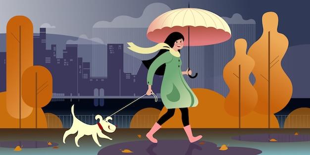 Uma menina sob um guarda-chuva anda com um cachorro em um parque de outono ao longo do aterro. cena de rua da cidade. Vetor Premium