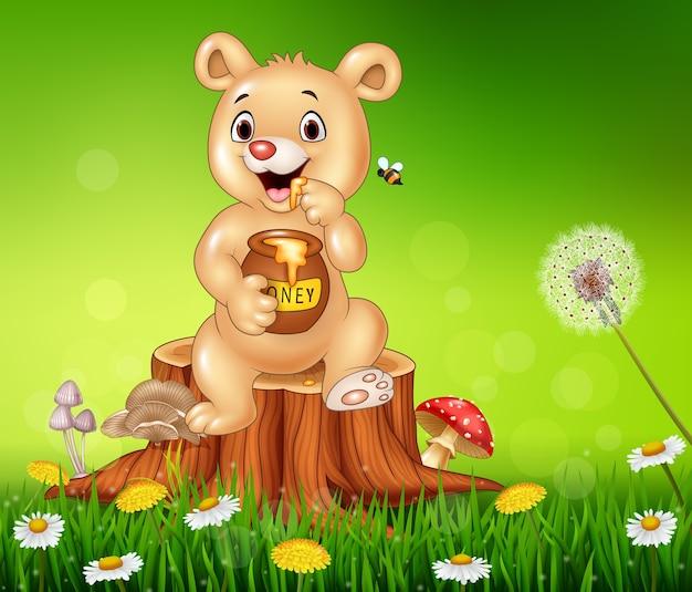 Urso de bebê fofo segurando mel no toco de árvore Vetor Premium