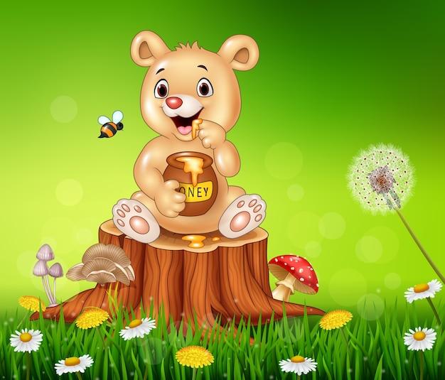 Urso pequeno bonito segurando mel no toco de árvore Vetor Premium