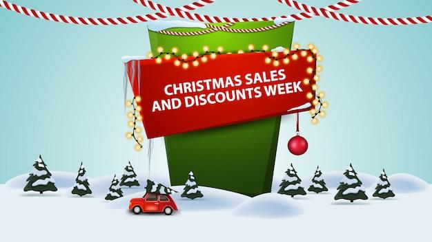 Vendas de natal e semana de desconto, banner de desconto dos desenhos animados com paisagem de inverno com carro antigo vermelho carregando a árvore de natal Vetor Premium