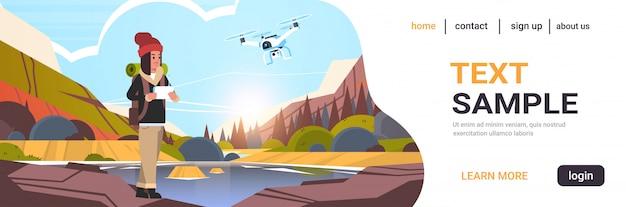 Viajante de mulher com mochila controlando drone usando o controle remoto Vetor Premium