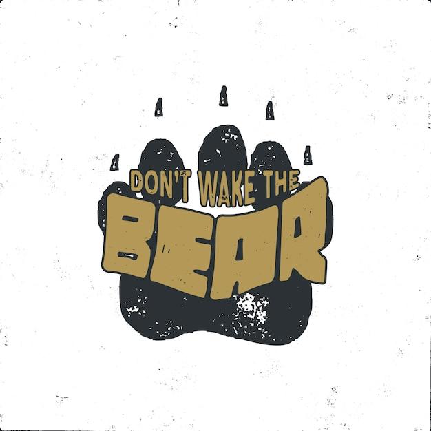 Vintage mão desenhada pegada de urso com citação de texto não acorde o urso. faixa animal estilo retro. Vetor Premium