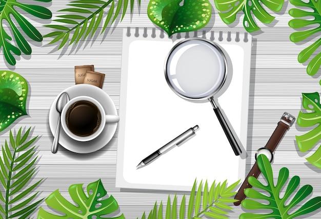 Vista superior da mesa de madeira com objetos de escritório e elemento de folhas Vetor grátis