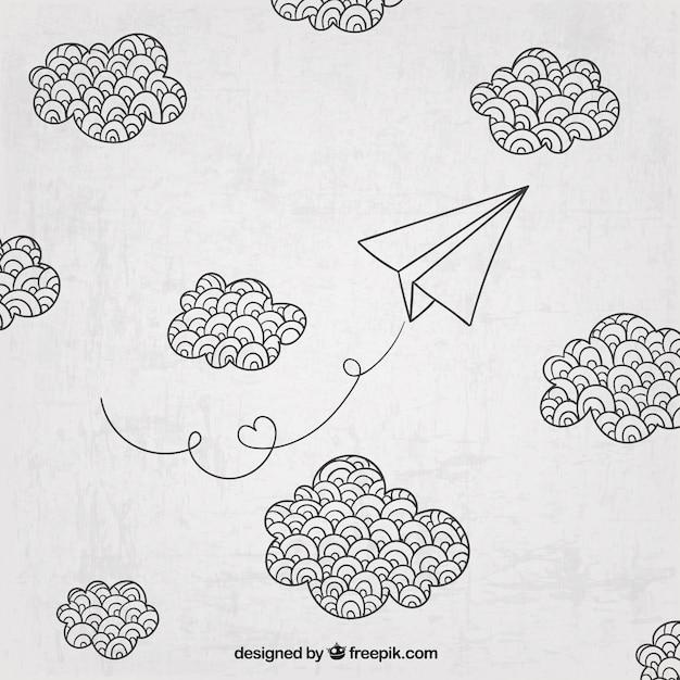 Aeroplano di carta disegnata a mano e nuvole Vettore gratuito