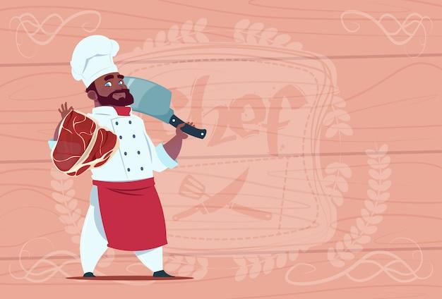 African american chef cook holding cleaver coltello e carne sorridente capo del fumetto in uniforme bianca del ristorante sopra fondo strutturato in legno Vettore Premium