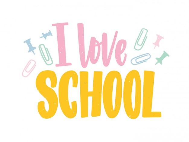 Amo la frase della scuola scritta con caratteri calligrafici colorati e decorata con graffette e puntine da disegno sparse. Vettore Premium