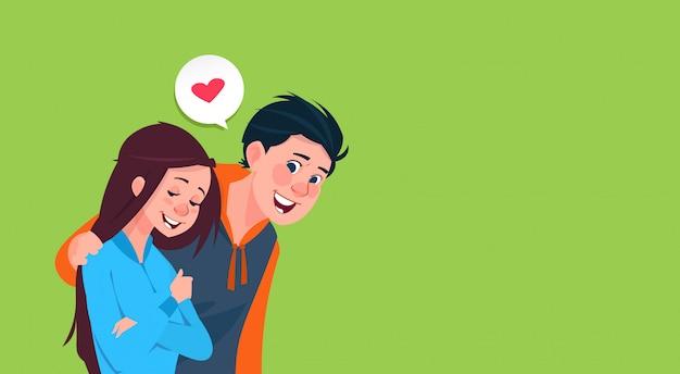 Anni dell'adolescenza di immagine di forma del cuore della ragazza di abbraccio del giovane ragazzo nell'insegna di amore con lo spazio della copia Vettore Premium