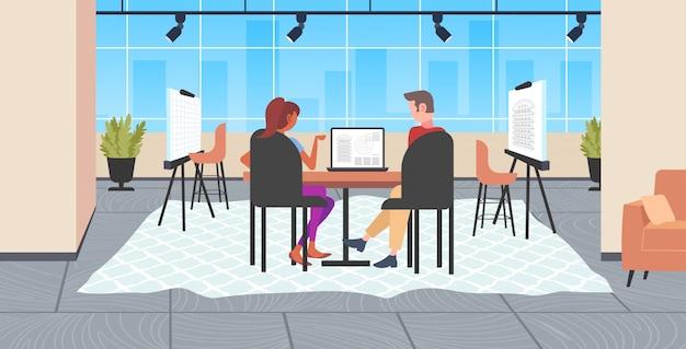 Architetti coppia usando laptop ingegneri redazione progetto casa sullo schermo del computer con progetti alloggiamento imprenditori ing piano casa moderna disegnatore studio interno a figura intera Vettore Premium