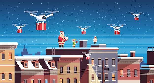 Babbo natale con elfi sul tetto tenere controller drone consegna presente servizio Vettore Premium