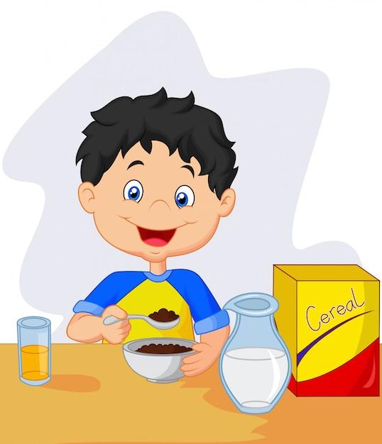 Bambina che mangia cereali per la colazione con latte Vettore Premium