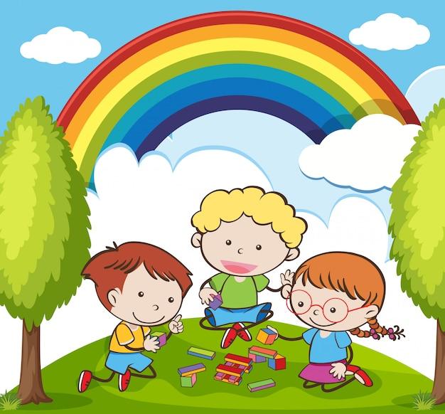 Bambini che giocano a mattoni nel giardino in bella giornata Vettore Premium