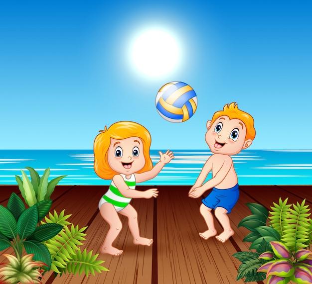 Bambini che giocano a pallavolo sul molo sul mare Vettore Premium