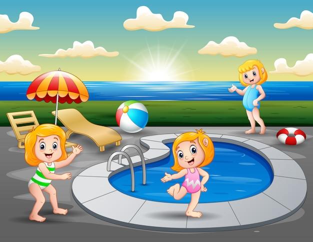 Bambini che giocano nella piscina all'aperto sulla spiaggia Vettore Premium
