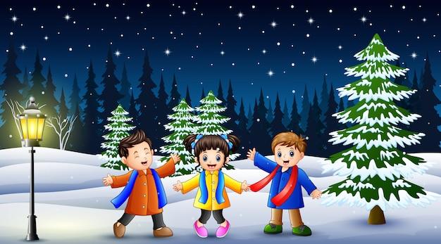Bambini felici che giocano nel paesaggio invernale di notte Vettore Premium