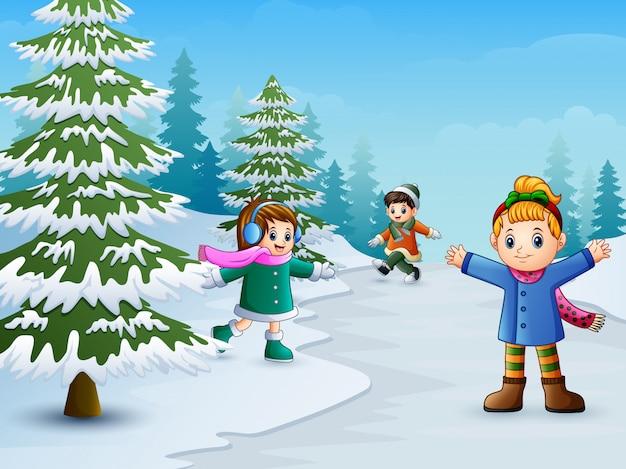 Bambini felici che giocano nel paesaggio invernale Vettore Premium