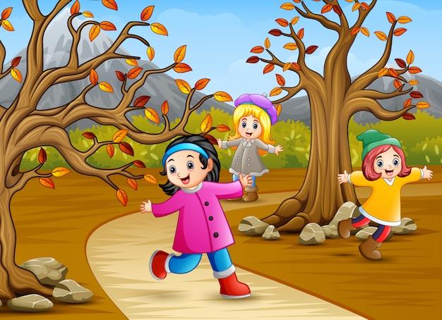 Bambini felici che giocano nel parco in autunno Vettore Premium