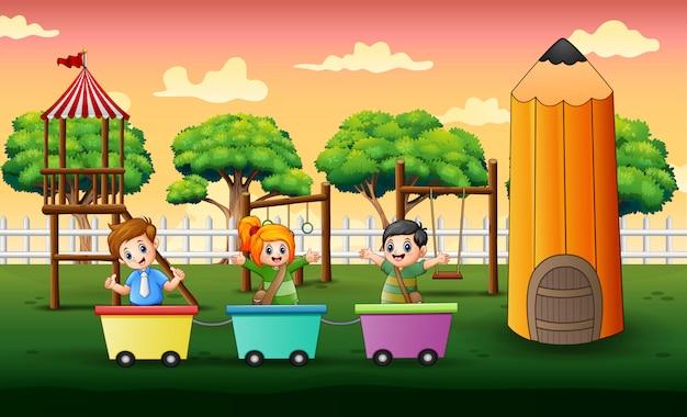 Bambini felici che giocano sul treno al parco giochi Vettore Premium