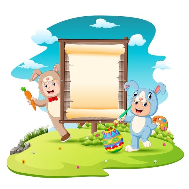 Bambini felici che indossano il costume del coniglietto e l'uovo della pittura con il fondo in bianco del segno Vettore Premium