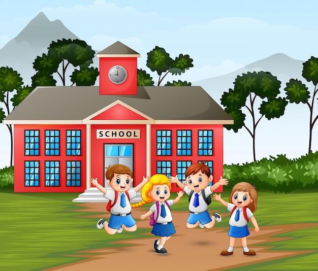 Bambini felici con lo zaino sull'edificio scolastico Vettore Premium