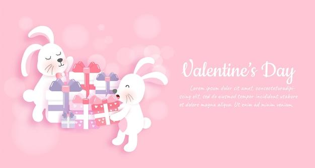 Banner di san valentino e lo sfondo con simpatici conigli e scatole regalo in carta tagliata stile Vettore Premium