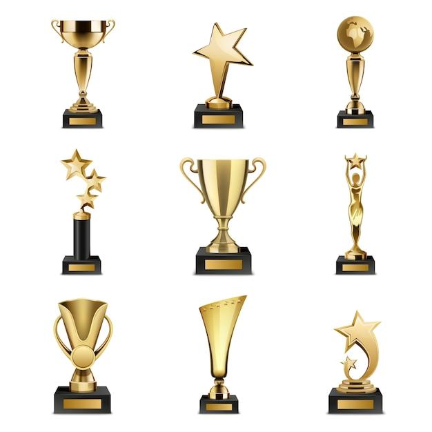 Belle coppe e premi dorati del trofeo dell'insieme realistico di forma differente isolati Vettore gratuito