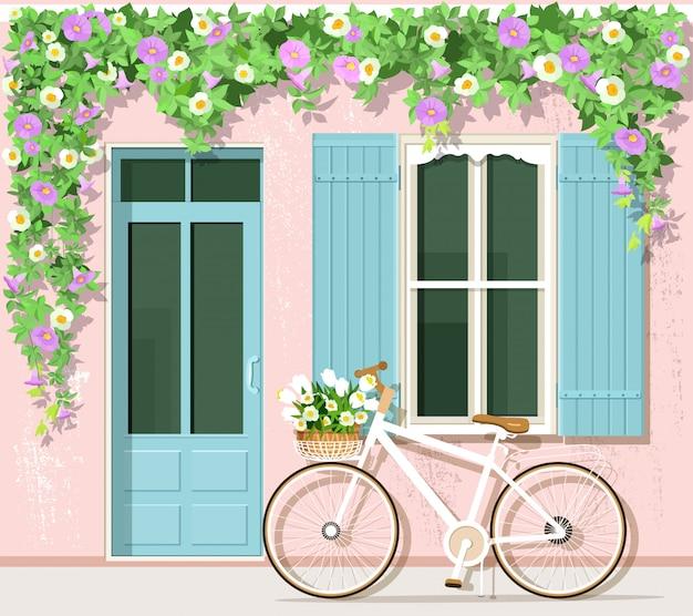 Bicicletta con fiori vicino alla casa in stile provenzale Vettore Premium
