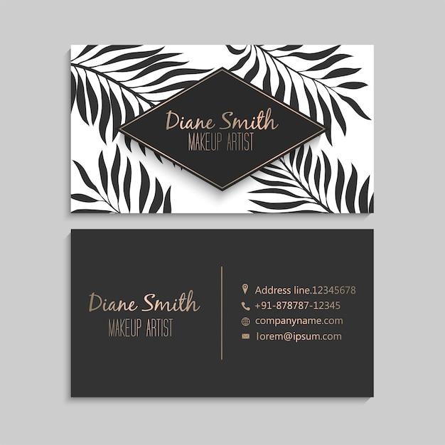 Biglietto da visita di lusso scuro e oro con foglie tropicali Vettore Premium