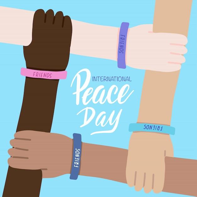 Biglietto di auguri per la giornata internazionale della pace. quattro mani di persone di razze diverse e incrociate insieme. amicizia mondiale. Vettore Premium