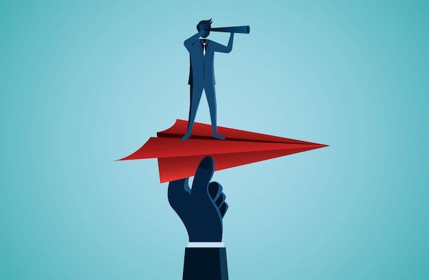 Binocolo della tenuta dell'uomo d'affari su un aereo di carta rosso Vettore Premium